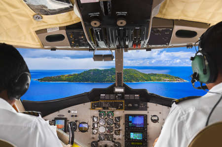 seychelles: Pilots in the plane cockpit and tropical island Editorial