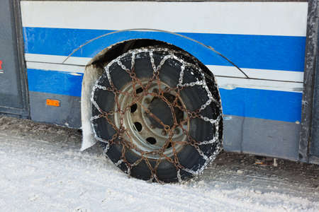 Snow chains on tyre of car - winter transportation photo