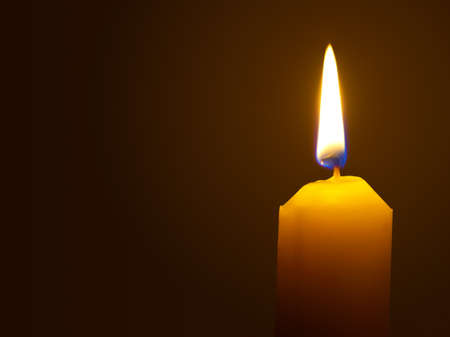 Macro of burning candle isolated on black background photo