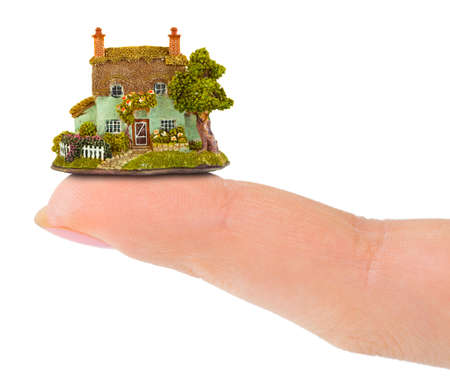 Finger and house isolated on white background photo