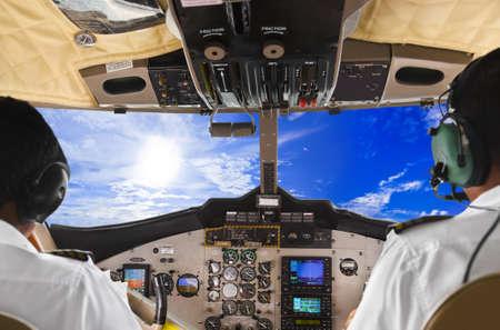 piloto: Los pilotos en la cabina del piloto plano y el cielo nublado