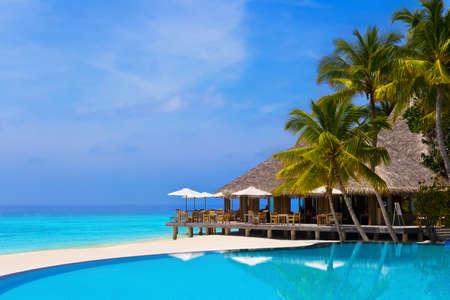 Caffè e la piscina su una spiaggia tropicale - sfondo di viaggio