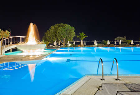 swiming: Water pool and fountain at night - vacation background