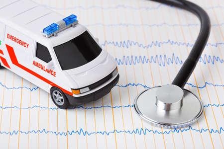 ambulance: Stethoscope and ambulance car on ecg - medical background Stock Photo