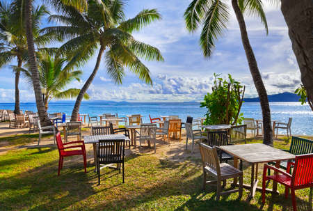 beach bar: Cafe and palms on a tropical beach - travel background