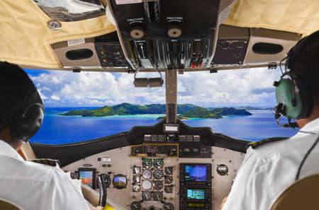 airplane landing: Pilots in the plane cockpit and tropical island Editorial