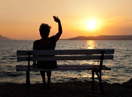 the farewell: Mujer en banco y la puesta del sol - fondo de vacaciones