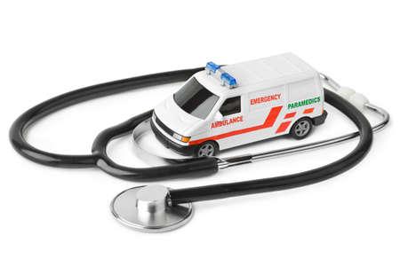 白い背景で隔離の聴診器とおもちゃの救急車車