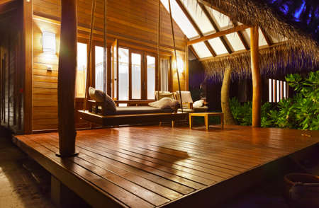 Beach Bungalow bij zonsondergang - Malediven vakantie achtergrond Redactioneel