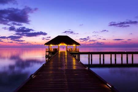 Water cafe bij zonsondergang - Malediven vakantie achtergrond
