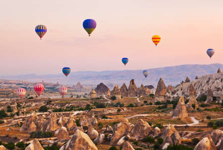 Hete luchtballon die over rotslandschap in Cappadocia Turkije Stockfoto - 38302879