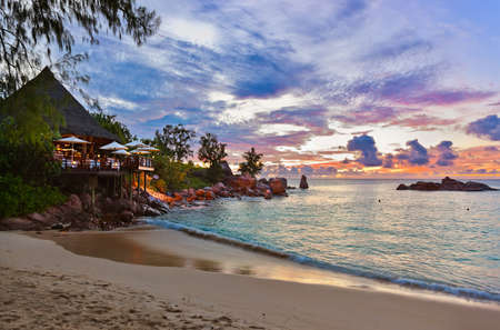 Cafe on Seychelles tropical beach at sunset - nature background 스톡 콘텐츠