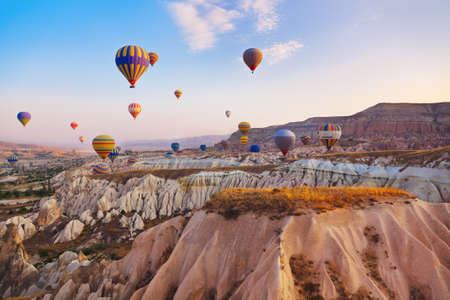 Hete luchtballon die over rotslandschap in Cappadocia Turkije Stockfoto