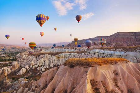 Hot air balloon flying over rock landscape at Cappadocia Turkey Foto de archivo