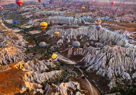 Hot air balloon flying over rock landscape at Cappadocia Turkey Stok Fotoğraf