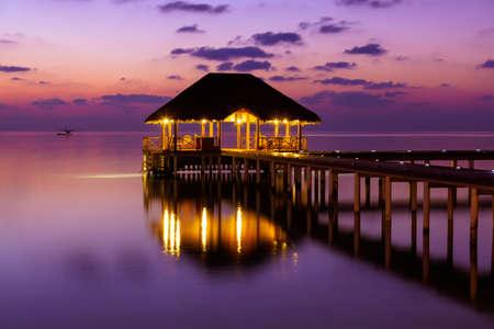 Water cafe bij zonsondergang - de Maldiven vakantie achtergrond