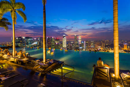 Pool on roof and Singapore city skyline - architecture and travel background Stock Photo - 56690501