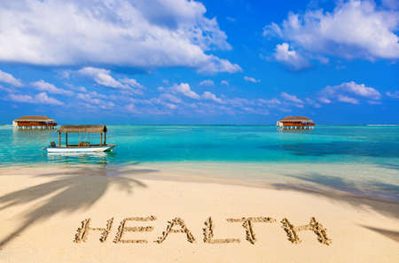 Word Health on beach - concept holiday background