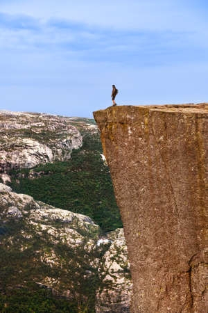Lonely man standing on cliff Preikestolen in fjord Lysefjord - Norway - nature and travel background Stok Fotoğraf