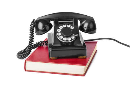 Vintage telephone and book isolated on white background