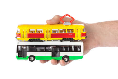 Hand with toy bus and tram isolated on white background 스톡 콘텐츠