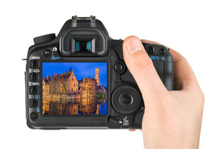 Hand with camera and Brugge cityscape - Belgium (my photo) isolated on white background