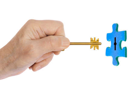 Hand with key and puzzle isolated on white background Stock Photo