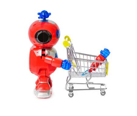 Robot de juguete y carrito de compras con mano aislado sobre fondo blanco. Foto de archivo