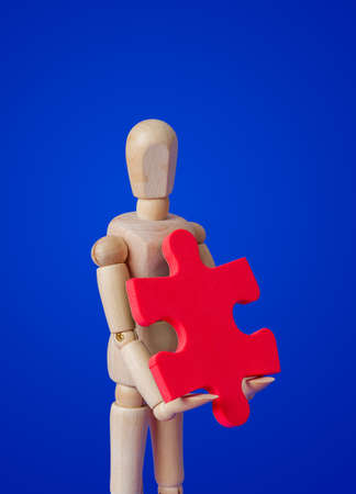 Wooden toy figure with puzzle on blue background