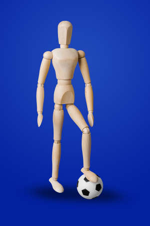 Football wooden toy figure on blue background
