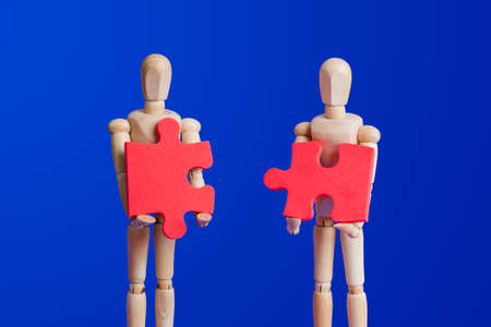 Wooden toy figures with puzzle on blue background Stock fotó