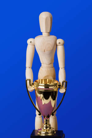 Wooden toy figure with golden trophy cup on blue background Reklamní fotografie