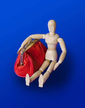 Wooden toy figure with red purse on blue background Standard-Bild - 122030796
