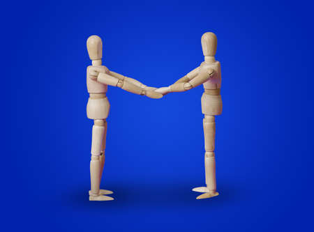 Wooden toy figures handshake on blue background Standard-Bild - 122028625