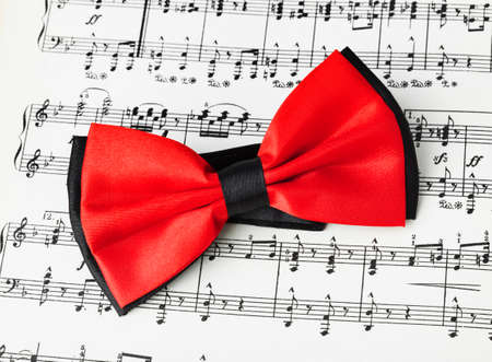 Red bow tie on music sheet - art background Standard-Bild - 122108279