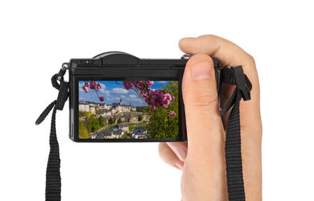 Hand with camera and Luxembourg city cityscape (my photo) isolated on white background
