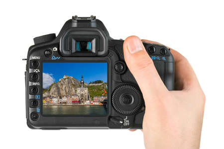 Hand with camera and Village Dinant in Belgium (my photo) isolated on white background