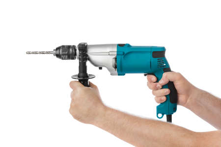 Electric drill in hands isolated on white background Фото со стока