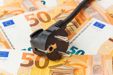 Electric plug on money euro - business technology background