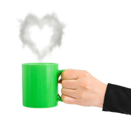 Hand with cup and steam like a heart isolated on white background