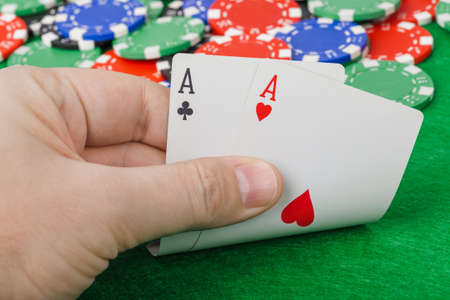 Hand with playing cards in casino - gambling background