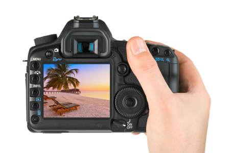 Mano con la macchina fotografica e la foto della spiaggia delle Maldive (la mia foto) isolata su fondo bianco