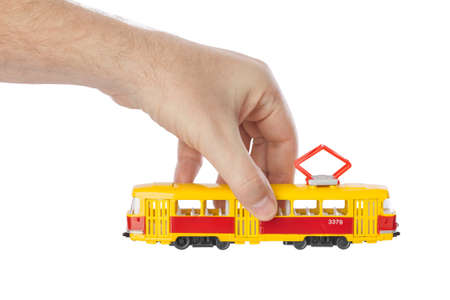 Hand with toy tram isolated on white background