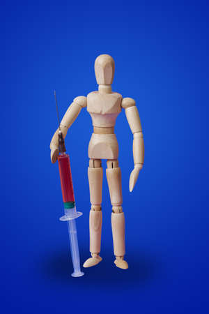 Wooden toy figure with syringe on blue background