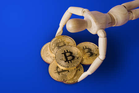 Wooden toy figure with bitcoins on blue background