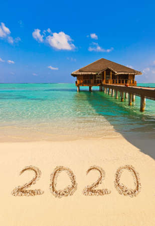 Numbers 2020 on beach - concept holiday background