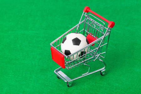 Soccer ball in shopping cart on green foorbal field 写真素材
