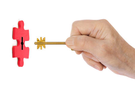 Hand with key and puzzle isolated on white background 写真素材
