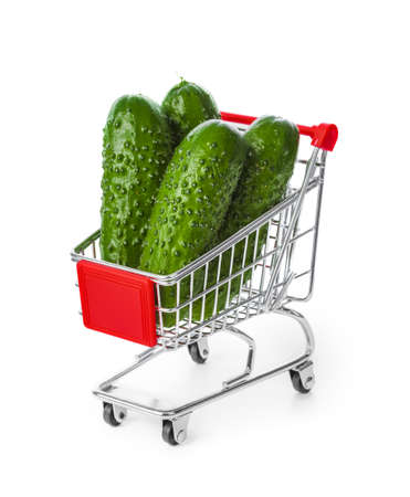 Fresh cucumbers in shopping cart isolated on white background