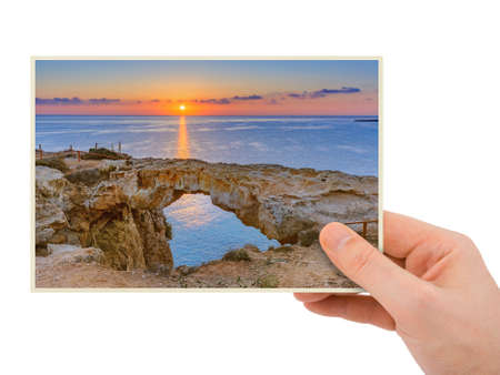 Hand and Famous stone Sin Bridge at sunrise in Ayia Napa Cyprus (my photo) isolated on white background